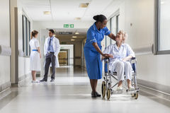 Senior Female Patient in Wheelchair & Nurse in Hospital. Senior female women patient in wheelchair sitting in hospital corridor with African American female Stock Images