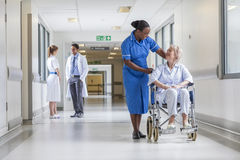 Senior Female Patient in Wheelchair & Nurse in Hospital Royalty Free Stock Photography