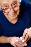 Senior female with pills Royalty Free Stock Photography