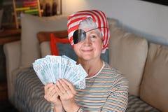 Senior female pirate holding bunch of money