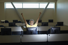 Senior Female Professor Celebrating Victory In Computer Classroom Royalty Free Stock Images