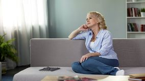 Senior female sitting on sofa and dreaming about summer vacation, retirement royalty free stock photo