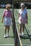 Senior Female Tennis Players Standing At Net stock photos