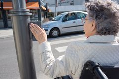 Senior female on wheelchair pushing button for traffic light stock photos