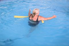 Senior female woman holds on to a flotation device on a swimming pool to learn how to swim. A senior female woman holds on to a flotation device on a swimming stock photography
