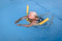 Senior female woman holds on to a flotation device on a swimming pool to learn how to swim. A senior female woman holds on to a flotation device on a swimming stock photo