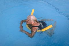 Senior female woman holds on to a flotation device on a swimming pool to learn how to swim. A senior female woman holds on to a flotation device on a swimming stock image