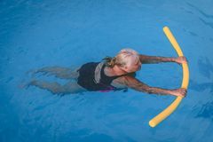 Senior female woman holds on to a flotation device on a swimming pool to learn how to swim. A senior female woman holds on to a flotation device on a swimming royalty free stock images