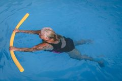 Senior female woman holds on to a flotation device on a swimming pool to learn how to swim. A senior female woman holds on to a flotation device on a swimming royalty free stock image