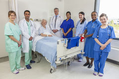 Senior Female Woman Patient Doctors & Nurses Medical Team. Senior female women patient in hospital bed surrounded by the multi ethnic interracial medical team of Royalty Free Stock Image