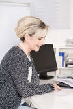 Senior female worker sitting at desk looking at business paper. Stock Photo