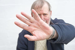 Senior fending off an attack. An image with selective focus  of a Senior's hand fending off a physical  attack Stock Photos