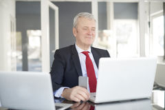 Senior financial analyst. Shot of an elderly financial businessman working on laptop royalty free stock photography