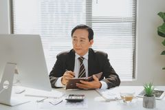 Senior financial asian businessman sitting at his workstation in. Front of computer Stock Photo