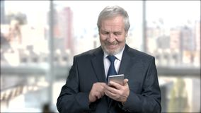 Senior financial manager texting a message. Elderly businessman answering the smartphone, send a mail and smiles for the beautiful job news. Business, office stock video