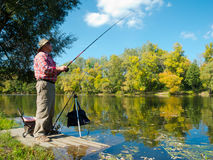 Senior fisherman catches a fish Stock Images