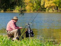 Senior fisherman catches a fish. In the river at the bait Royalty Free Stock Images