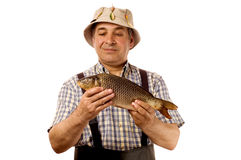 Senior fisherman with his catch. (isolated on white royalty free stock image