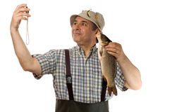 Senior fisherman with his catch Royalty Free Stock Photography