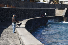 Senior fisherman and his dog fishing on a pier Royalty Free Stock Image