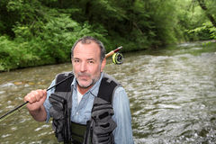 Senior fisherman passionate about river fishing Stock Photos