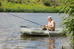 Senior fisherman rowing as he trolls his line Stock Photos