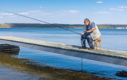 Senior fisherman sitting on a pier Royalty Free Stock Photos