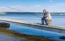 Senior fisherman sitting on a pier Royalty Free Stock Photos