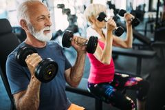 Mature fit couple exercising in gym to stay healthy royalty free stock image