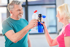 Senior fitness couple holding bottles with water gym. Side view of senior fitness couple holding bottles with water gym stock photography