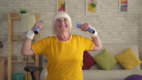 Senior fitness old woman posing with dumbbells and looking at camera smiling. Slow mo stock video footage