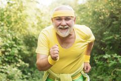 Senior fitness person running in park for good health. Senior man running in sunny nature. Healthy lifestyle concept