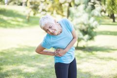 Senior fitness woman rubbing muscles of her right side stock photo