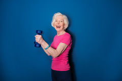 Senior fitness woman training with dumbbells  on blue. Happy senior fitness woman training with dumbbells  on blue Royalty Free Stock Photography