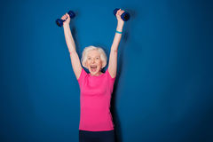 Senior fitness woman training with dumbbells isolated on blue. Excited senior fitness woman training with dumbbells isolated on blue Stock Photos