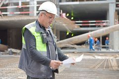 Senior Foreman At Consruction Site. Senior Foreman at construction site is inspecting ongoing production according to design drawing stock images