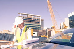 Senior foreman in glasses doing his job at building area on car Stock Photo