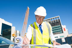 Senior foreman in glasses doing his job at building area on car hood Royalty Free Stock Images