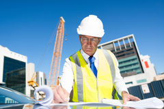 Senior foreman in glasses doing his job at building area on car hood Royalty Free Stock Photography