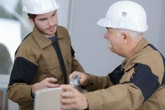 Senior foreman sharing ideas with young builder Stock Photography