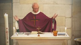 A Senior French Catholic priest is giving mass during a baptism in Aquitaine stock photography