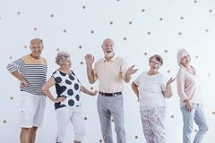 Senior friends celebrating birthday. Senior men and his friends celebrating his birthday against wallpaper with gold dots stock photo