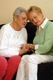 Senior friends comfort/prayer. Two senior women girlfriends/sisters eyes closed holding hands comforting each other stock images