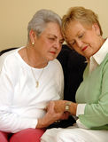 Senior friends comfort/prayer. Two senior women girlfriends/sisters eyes closed holding hands comforting each other Royalty Free Stock Image