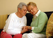 Senior friends comfort/prayer. Two senior women girlfriends/sisters eyes closed holding hands comforting each other stock photos