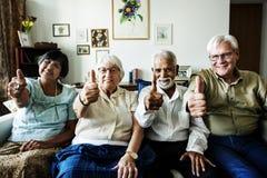 Senior friends gesturing thumbs up stock photo