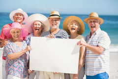 Senior friends holding blank paper. On a sunny day Royalty Free Stock Image