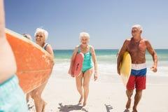 Senior friends holding surfboard Stock Image