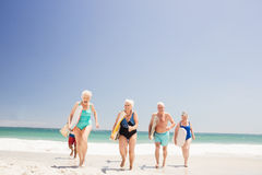 Senior friends holding surfboard. On the beach Stock Image
