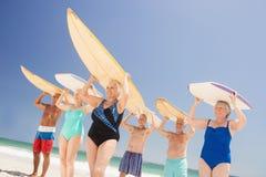 Senior friends holding surfboard. On the beach Stock Photo